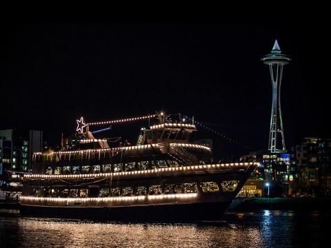 阿戈西圣诞船和篝火活动期间飘荡在太空针塔前河面上的一艘光彩夺目的船只