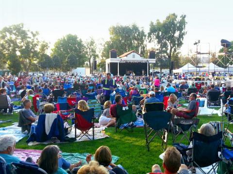 在卡马里奥艺术委员会举办的夏季公园系列音乐会中,人们在户外欣赏现场音乐表演
