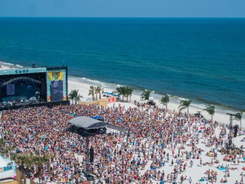 阿拉巴马州墨西哥湾海岸的巢穴音乐节期间,在海滩上欣赏现场乐队演奏