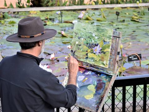 德克萨斯州的 EnPleinAirTEXAS National Competition & Cinch Roping Fiesta 全国赛和嘉年华期间,一位艺术家在公民联盟公园画睡莲